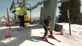 faaliyetler : Snowboarder and small child get off chairlift