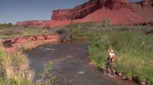 rybář : fly fisherman catches trout with red rock cliffs in distance Dostupné videozáznamy