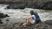 A girl with a backpack sits on the bank. Below her feet, a stream is bubbling.