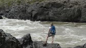 пеший турист : A girl with a backpack is standing on the rock. Below her feet, a stream is bubbling. Стоковые видеозаписи