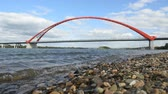Waves on the bank of the river Ob, in the background a red arch of the Bugrinsky bridge. Vídeos