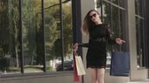 kurban : Glamorous young woman spins around on the street after shopping