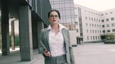 срочный : Young business woman walking to the office building Стоковые видеозаписи