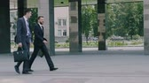 同僚 : Two confident young businessmen are walking in the urban environment to the office building