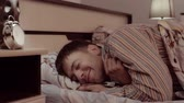 awaking : Young man goes to bad and smiles, but suddenly opens his eyes widely Stock Footage