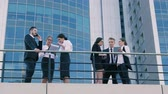 hırslı : Coworkers standing outdoors and having hot discussion on a busy working day