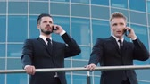 mobility : Two business men standing near the banister and speaking on the phone Stock Footage