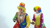psychopath : Two circus clowns throwing up a toy- pancake and catching it usin frying pans Stock Footage