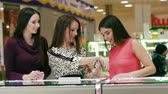Чикаго : Three attractive women in beautiful dresses looking at accessories in the jewelry store Стоковые видеозаписи