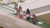 farra : Three female friends in shopping center moving down on escalator