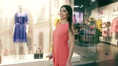 блаженный : Attractive confident young woman turning round while walking along clothes stores