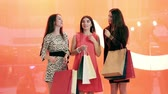 女らしさ : Portrait of three young women talking to each other in shopping centre 動画素材