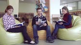 listening post : Group of students in library reading the books Stock Footage