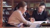 acessibilidade : Three young students preparing research together in library