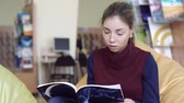 educacion superior : Portrait of girl in library studying articles of a book