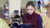 ders kitabı : Female student reading a book attentively while sitting in a library