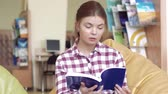 estante : Young fair-skinned university girl reading a book to find information