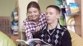 образовательный : Two young friendly students looking through a book together