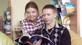 hispanic : Smiling students in library enjoying a chosen book