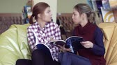 listening post : Two concentrated university girls in reading-room discussing the article Stock Footage