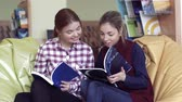 listening post : A couple of surprised female students discussing a book