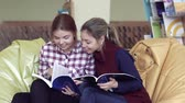 estante : Two pretty university girls sitting in library and looking into books