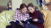 estante : Two smiling female students thumbing through funny magazines Vídeos