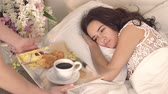 bed and breakfast : Close-up of happy young woman getting coffee in bed from her caring husband