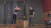 engradado : Attractive sports people box jumps while working out in gym