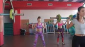 snatch : Quats with weights on training. Group of young women and man in aerobics class making exercises. Girls with barbells. Healthy lifestyle in fitness center. Stock Footage