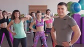 aeróbica : Close-up of male fitness trainer. He looks at a group of girls who train in an aerobic gym Stock Footage