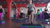 shaping : fitness, sport, training, gym and lifestyle concept - group of women working out with steppers in gym Stock Footage