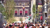 Mexico City, CIRCA June 2018 SLOW MOTION: Cheerleader jumps and makes an acrobatic movement in the air. Around her, a crowd walks in the street. Stok Video
