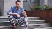 distante : Online Video Chat by Casual Man Sitting on Stairs Stock Footage