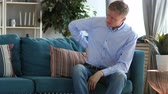 támogatás : Middle Aged Man with Back Spinal Pain Sitting on Couch