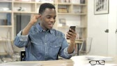 Excited African Man Enjoying Success while Using Smartphone