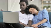usar : African Man Working on Laptop with Sleeping Girlfriend on Shoulder