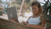 hamak : Woman freelancer works on the beach in hammock
