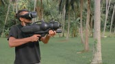 senhor : Man with weapon playing virtual reality game in the jungle Vídeos