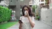 girl walking on city streets and drinking coffee to go in super slow motion Stock Footage