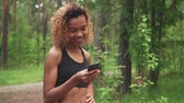 cabelos cacheados : young beautiful African American woman with curly hair is chatting in her phone before jogging
