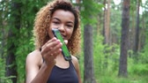 запустить : Black young woman using her smartphone after jogging and shows green screen to the camera
