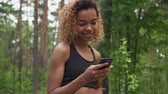афроамериканца : Black young woman using smartphone after jogging and shows green screen to the camera in slow motion