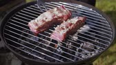 cook lays raw ribs on barbecue grill