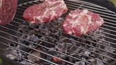 Cooking juicy raw meat steaks on the bbq grill