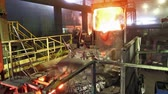 heavy : Workers operates in blast furnace workshop of metallurgical plant, foundry. Red color is a reflection of the molten metal. Stock Footage