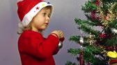 expression : Portrait of a lovely little girl who is wearing Santa hat, standing against the Christmas background.