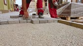 flagstone : Masons hands are fitting flagstone. Close up view of construction workers hands until hes paving street.