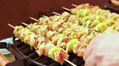 broiling : BBQ barbecuing skewers, grill with vegetable skewer - close up. Grilled gourmand chicken skewers are made with white meat, bacon and pieces of green paprika being turned on the BBQ. Stock Footage