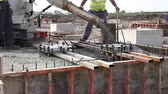 instalator : Pouring reinforced concrete. Workers at building site are pouring concrete in armored cage frame.